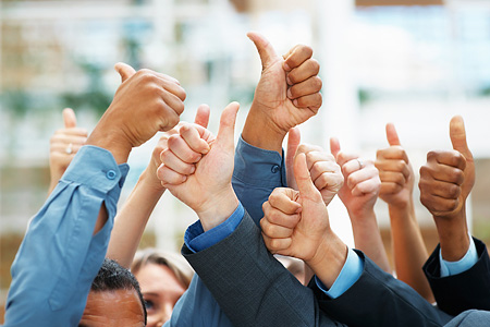 Photo of many office workers with thumbs up in the air